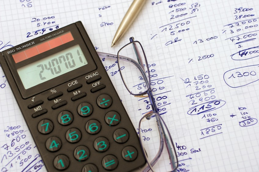 Taschenrechner und Rechenblock mit vielen Zahlen