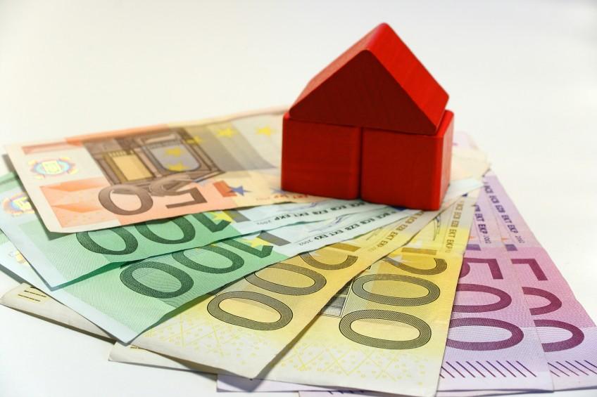 Haus aus Bauklötzen steht auf mehreren größeren Geldscheinen