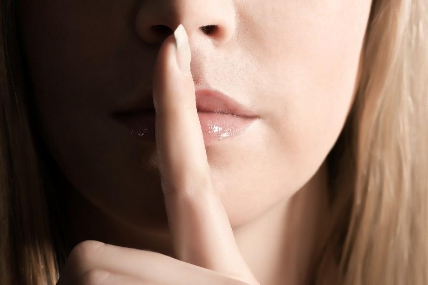 Gesichtsausschnitt einer jungen Frau, die einen Finger über die Lippen legt