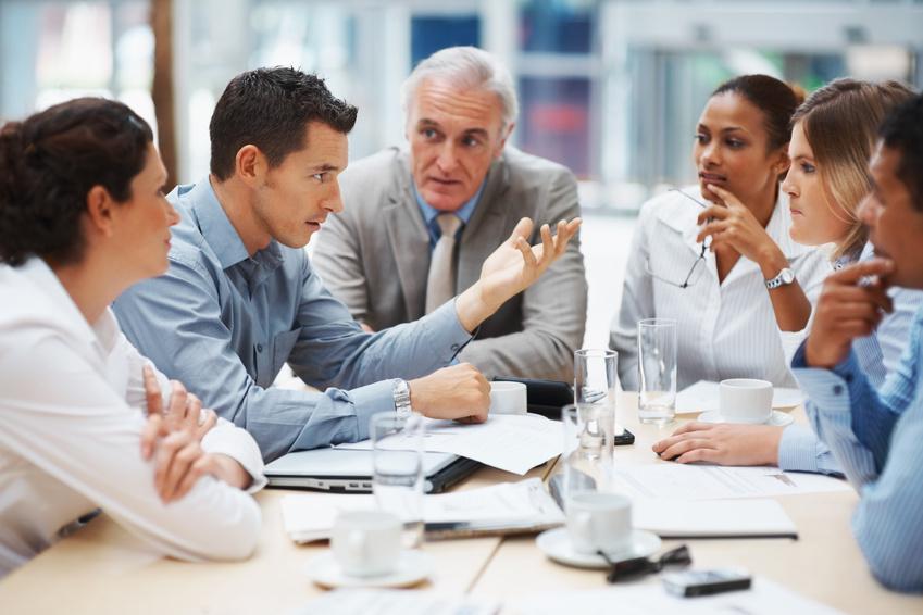 Menschen sitzen am Tisch und diskutieren