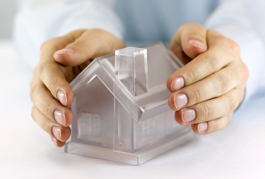 Hände einer Hausverwaltung umschließen ein Modellhaus
