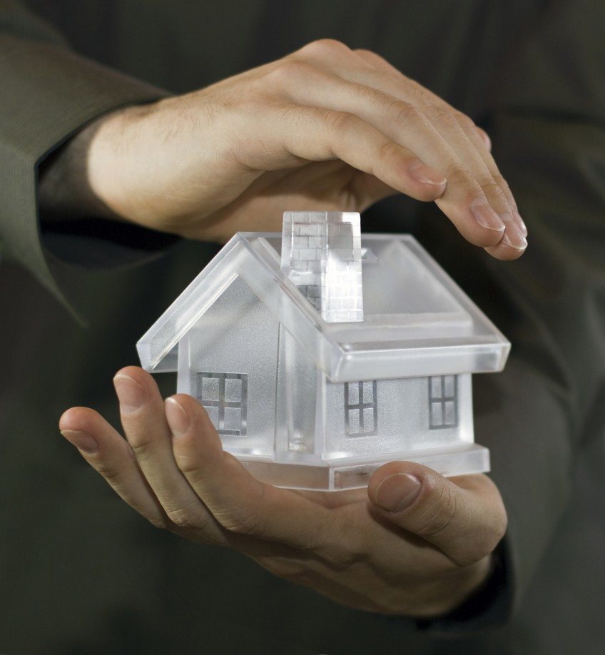 Ein Immobilienverwalter hält ein Modellhaus in seinen Händen, die eine Hand schützend darüber gehalten.
