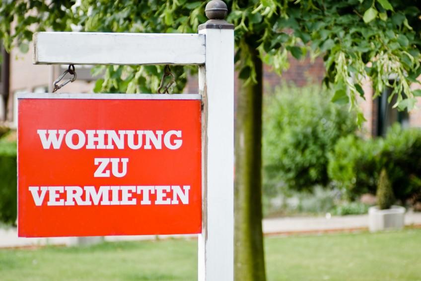 """Hübsches Schild mit der Aufschrift """"Wohnung zu vermieten"""" vor Bäumen. Im Hintergrund zeichnet sich ein Mietshaus ab."""