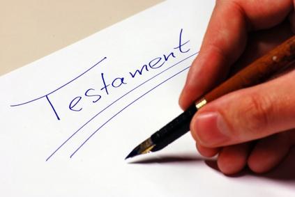 Hand mit Feder schreibt das Wort Testament. Vererbt wird Wohnungseigentum.